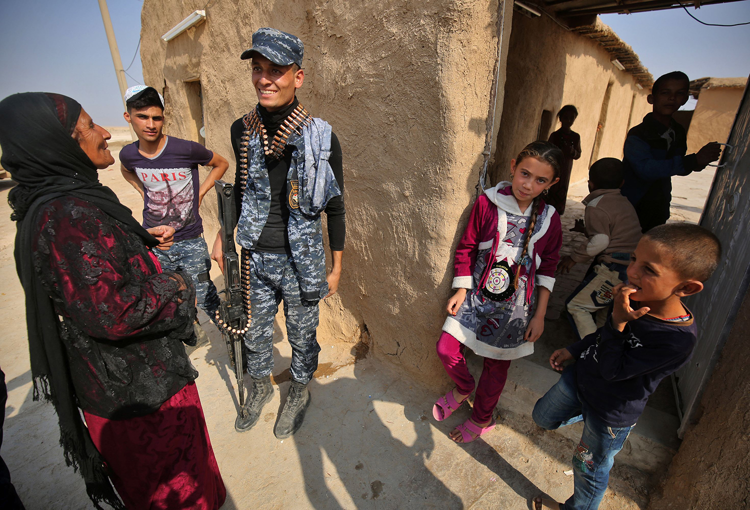A member of the Iraqi forces talks with a family in the village of al-Khuwayn, south of Mosul, after recapturing it from Islamic State (IS) group jihadists on October 23, 2016, in part of an ongoing operation to tighten the noose around Mosul and reclaim the last major Iraqi city under IS control. / AFP PHOTO / AHMAD AL-RUBAYE / TT / kod 444