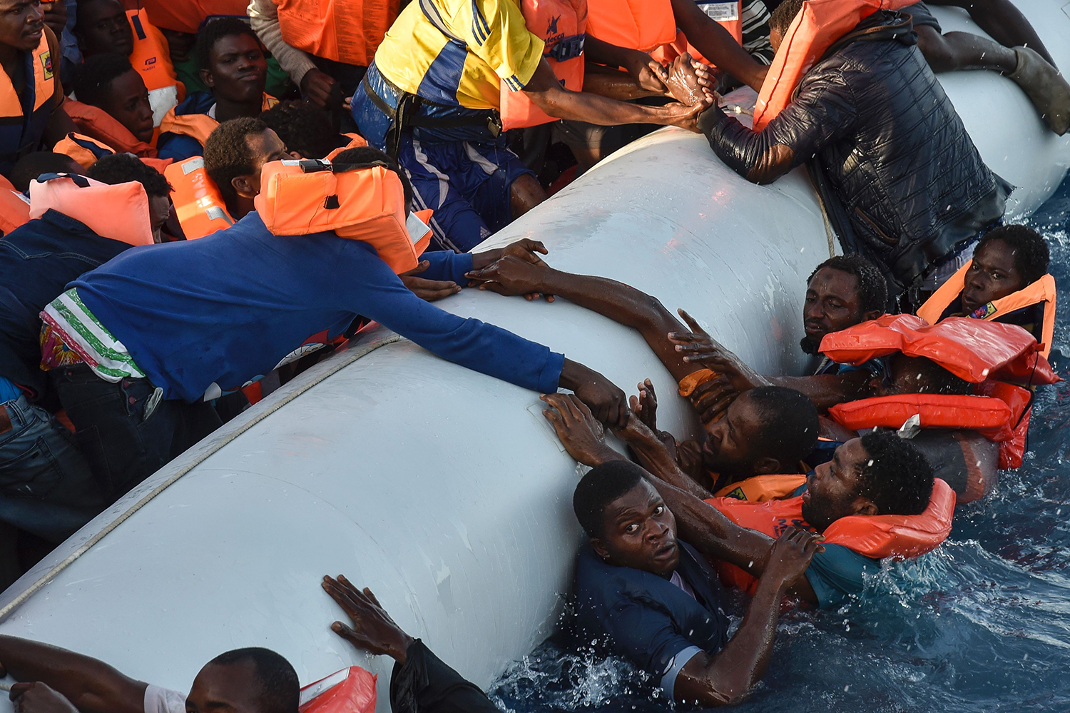 Migrants and refugees panic as they fall in the water during a rescue operation of the Topaz Responder rescue ship run by Maltese NGO Moas and Italian Red Cross, off the Libyan coast in the Mediterranean Sea, on November 3, 2016. / AFP PHOTO / ANDREAS SOLARO / TT / kod 444