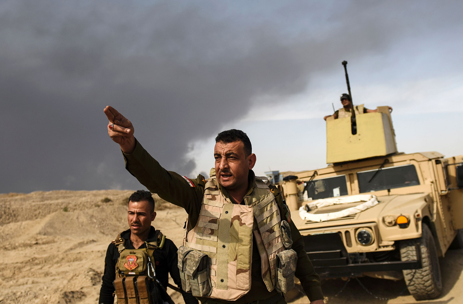 "TOPSHOT - CORRECTION - A member of Iraqi forces gestures as troops head to the frontline on October 18, 2016 near the town of Qayyarah, south of Mosul, during the operation to recapture the city from the Islamic State group. Tens of thousands of Iraqi forces were making gains on the Islamic State group in Mosul in an offensive US President Barack Obama warned would be a ""difficult fight"". A massive cloud of dark grey smoke blots out the horizon as the result of oil wells being set afire by IS in an effort to provide cover from air strikes. / AFP PHOTO / BULENT KILIC / ""The erroneous mention[s] appearing in the metadata of this photo by BULENT KILIC has been modified in AFP systems in the following manner: [date is October 18] instead of [October 16]. Please immediately remove the erroneous mention[s] from all your online services and delete it (them) from your servers. If you have been authorized by AFP to distribute it (them) to third parties, please ensure that the same actions are carried out by them. Failure to promptly comply with these instructions will entail liability on your part for any continued or post notification usage. Therefore we thank you very much for all your attention and prompt action. We are sorry for the inconvenience this notification may cause and remain at your disposal for any further information you may require."" / TT / kod 444"