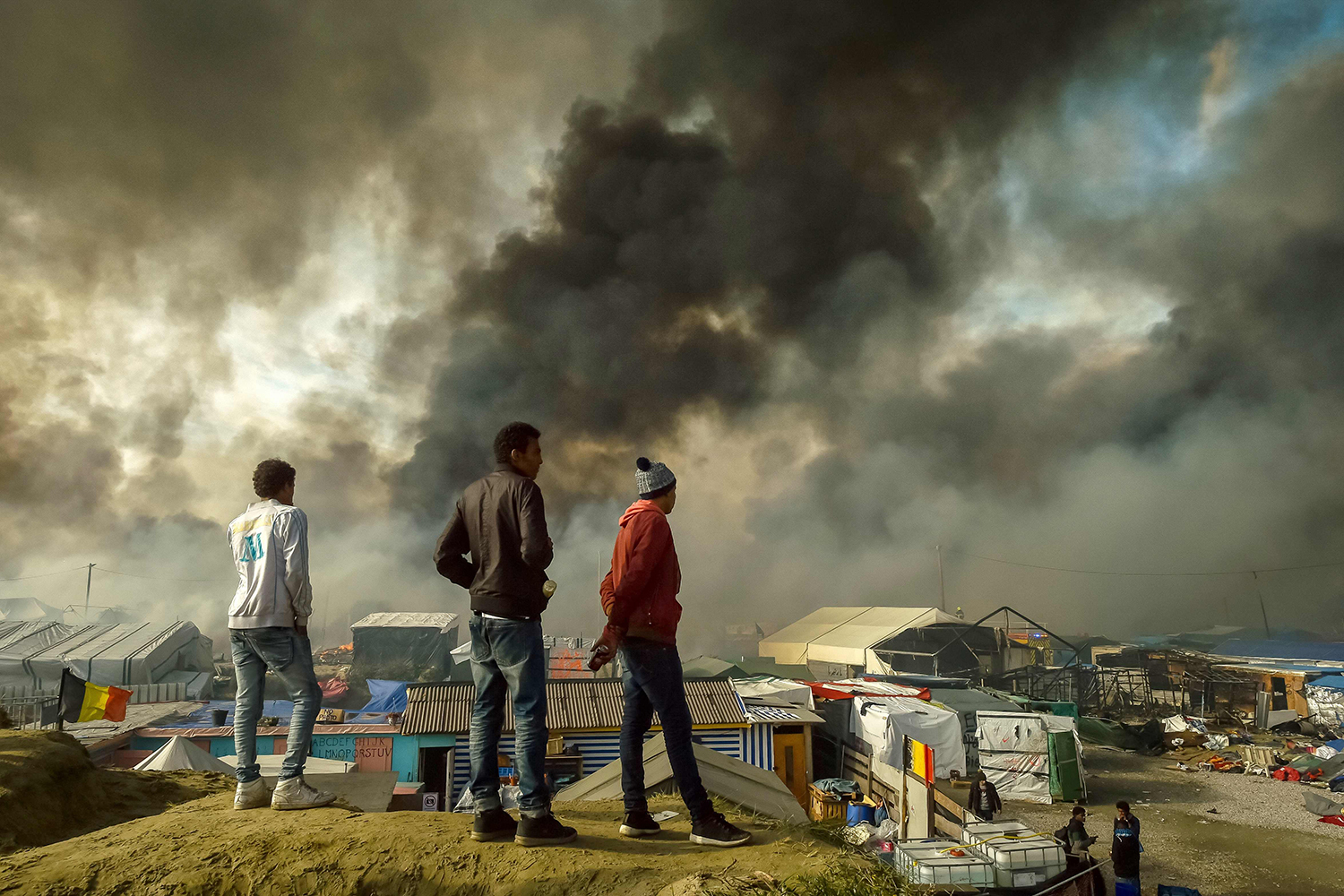 "TOPSHOT - Migrants stand on a hill overlooking the ""Jungle"" migrant camp in Calais, northern France, as smoke rises on October 26, 2016 during a massive operation to clear the squalid settlement where 6,000-8,000 people have been living in dire conditions. Fresh fires broke out on October 26 in the ""Jungle"" migrant camp on the second day of operations to dismantle the squalid settlement in northern France. Smoke billowed over the sprawling camp near Calais for a second day amid fears that abandoned gas cylinders could explode. / AFP PHOTO / PHILIPPE HUGUEN / TT / kod 444"