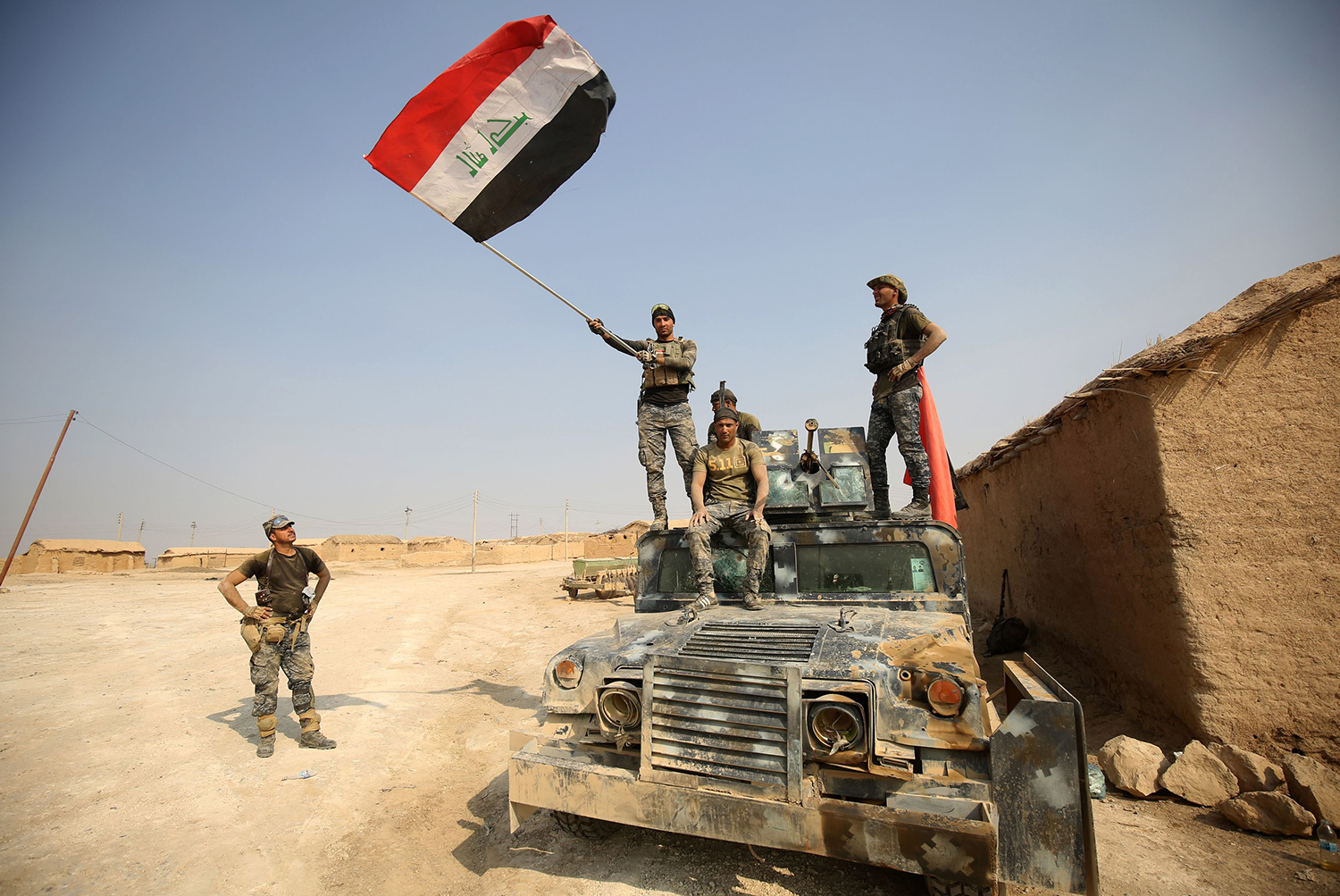 TOPSHOT - Iraqi government forces raise their national flag as they enter the village of al-Khuwayn, south of Mosul, after recapturing it from Islamic State (IS) group jihadists on October 23, 2016, in part of an ongoing operation to tighten the noose around Mosul and reclaim the last major Iraqi city under IS control. / AFP PHOTO / AHMAD AL-RUBAYE / TT / kod 444