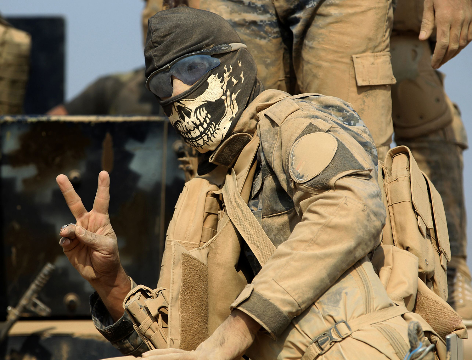 TOPSHOT - A member of the Iraqi government forces flashes the sign for victory as they enter the village of al-Khuwayn, south of Mosul, after recapturing the village from Islamic State (IS) group jihadists on October 23, 2016, in part of an ongoing operation to tighten the noose around Mosul and reclaim the last major Iraqi city under IS control. / AFP PHOTO / AHMAD AL-RUBAYE / TT / kod 444