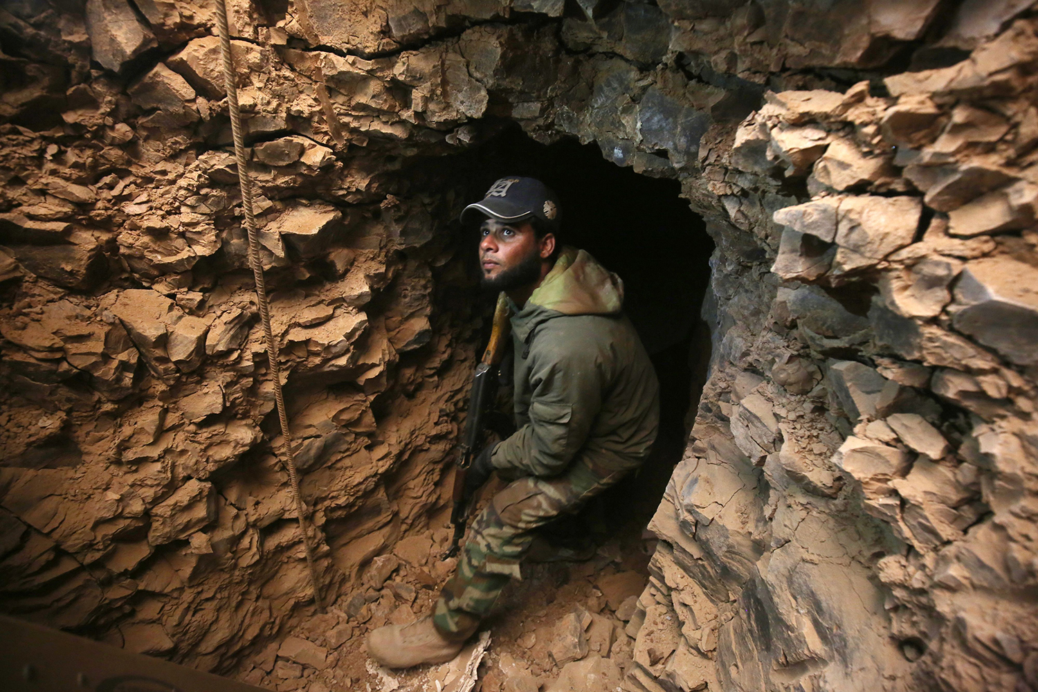 TOPSHOT - An Iraqi Shiite fighter from the Hashed al-Shaabi (Popular Mobilisation) paramilitary forces inspects an underground tunnel in the town of Tal Abtah, south of Tal Afar, on December 10, 2016, after they retook the area during a broad offencive to retake the city of Mosul from Islamic State (IS) jihadists. Hashed al-Shaabi (Popular Mobilisation) paramilitary forces have made progress in recent weeks on a western front targeting Tal Afar town on the road linking Mosul to Syria. On December 8, 2016, the paramilitary forces were clearing Tal Abtah of bombs and booby traps after a fierce, days-long fight to retake it. / AFP PHOTO / AHMAD AL-RUBAYE / TT / kod 444