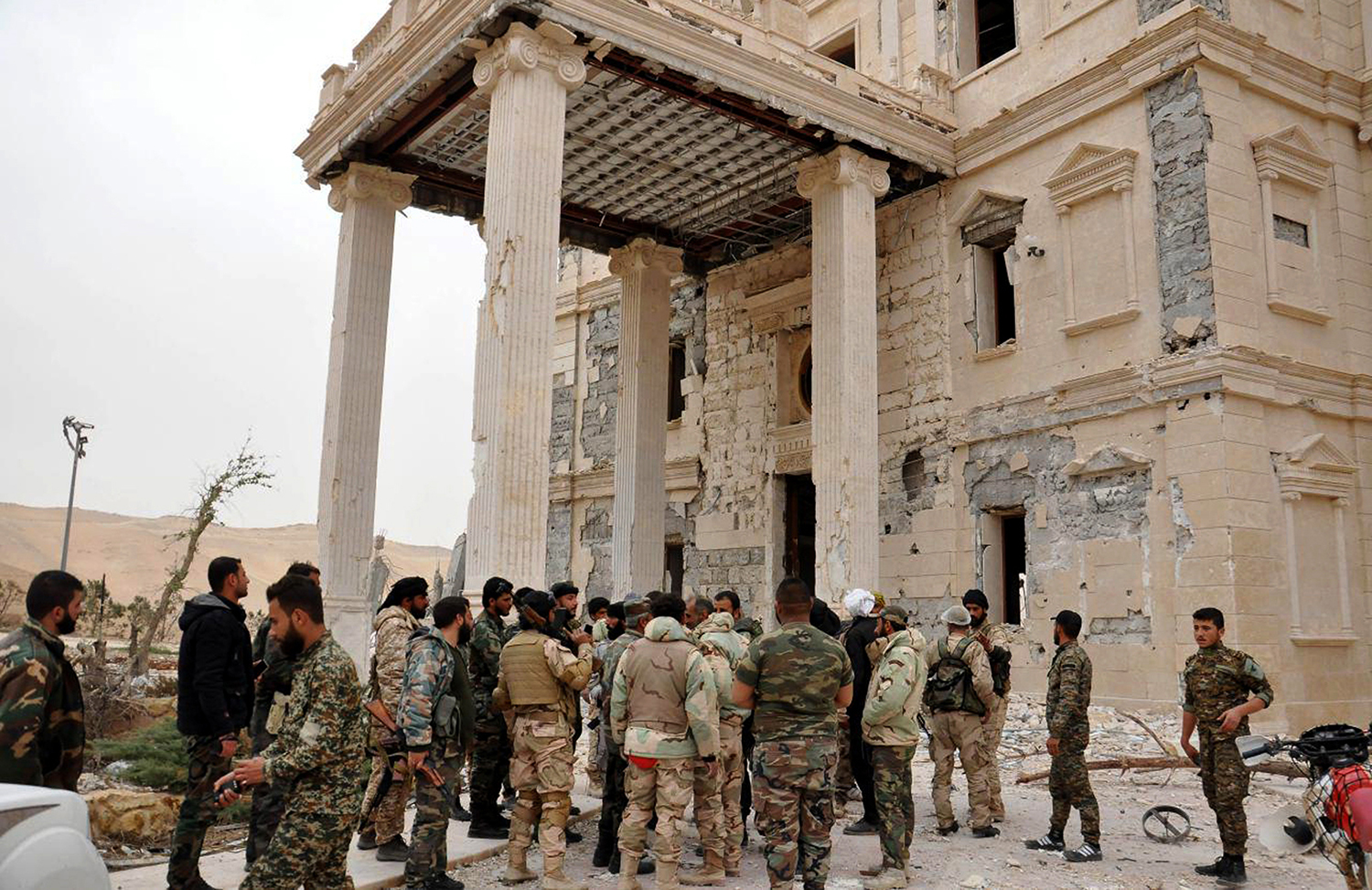 FILE -- In this file photo released March 24, 2016, by the Syrian official news agency SANA, Syrian government soldiers gather outside a damaged palace, in Palmyra, central Syria. Palmyra, the archaeological gem that Islamic State fighters retook Sunday, Dec. 11, 2016, from Syrian troops is a desert oasis surrounded by palm trees, and a UNESCO world heritage site, that boasts 2,000-year-old towering Roman-era colonnades and priceless artifacts. It is also a strategic crossroads linking the Syrian capital, Damascus, with the country's east and neighboring Iraq. (SANA via AP, File)