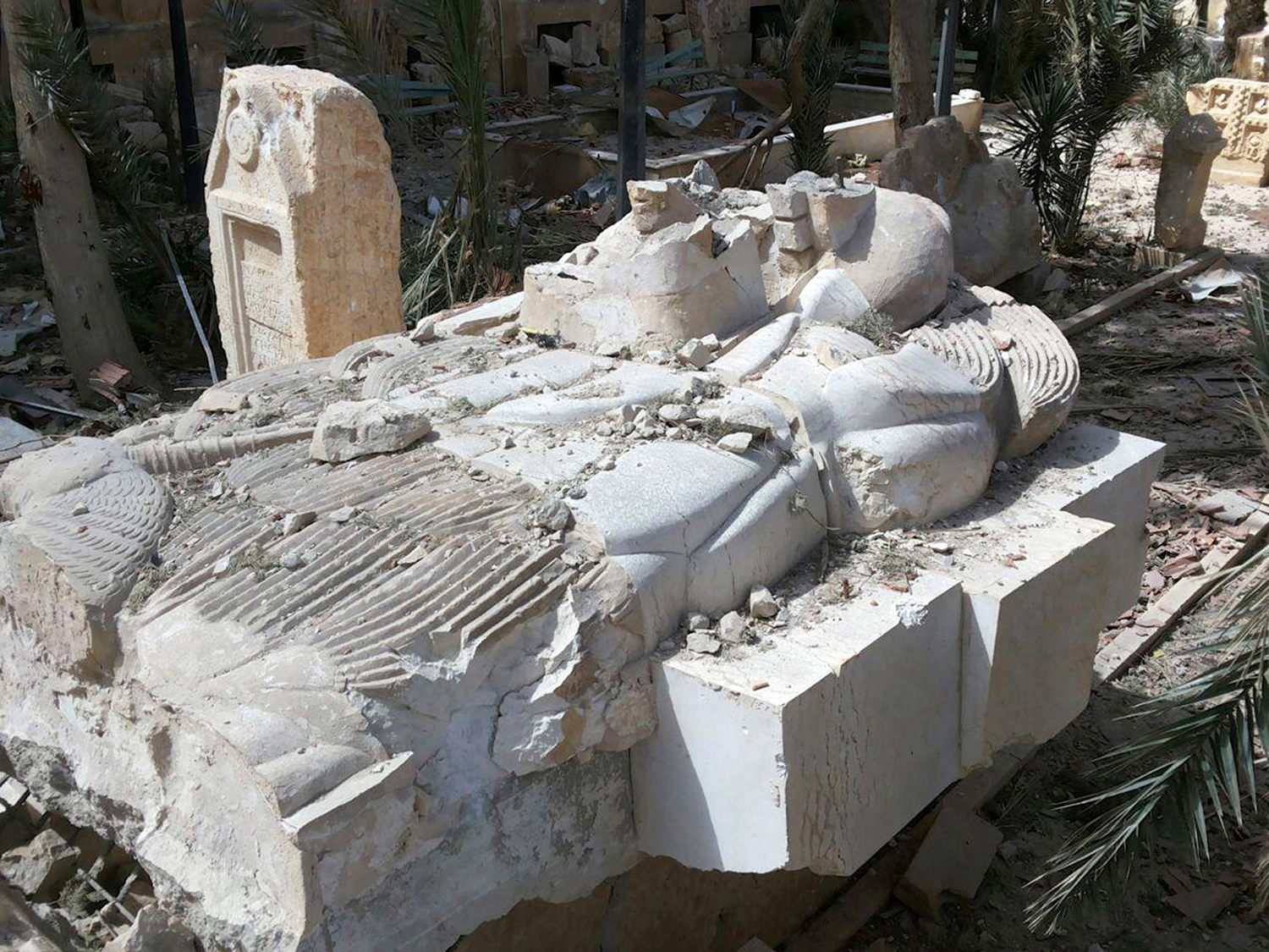 FILE - This file photo released March 27, 2016, by the Syrian official news agency SANA, shows a destroyed statue outside the damaged Palmyra Museum, in Palmyra city, central Syria. Palmyra, the archaeological gem that Islamic State fighters retook Sunday, Dec. 11, 2016, from Syrian troops, is a desert oasis surrounded by palm trees, and a UNESCO world heritage site, that boasts 2,000-year-old towering Roman-era colonnades and priceless artifacts. It is also a strategic crossroads linking the Syrian capital, Damascus, with the country's east and neighboring Iraq. (SANA via AP, File)