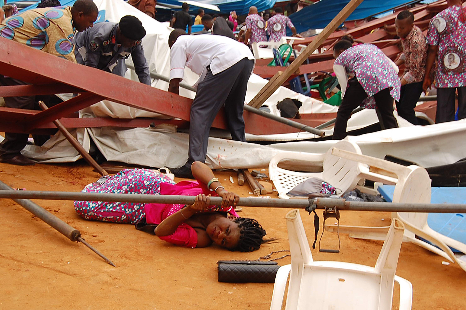 TOPSHOT - This picture taken on December 10, 2016 shows a woman stuck under a scaffolding bar amid rubbles at the scene after an evengelical church roof collapsed on worshippers in the remote southeastern city of Uyo, the capital of Akwa Ibom state. The search for survivors continued after a church roof collapsed killing at least 60 people, with many more feared dead. / AFP PHOTO / STRINGER / TT / kod 444