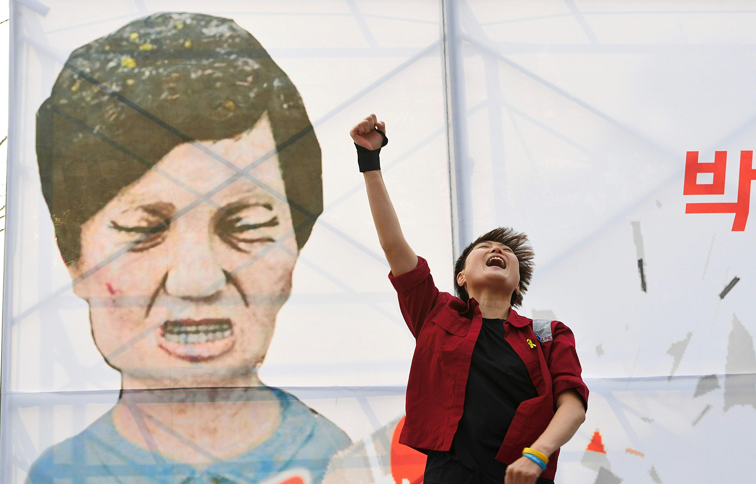TOPSHOT - A protester shouts slogans in front of a caricature of South Korea's President Park Geun-Hye during a rally urging the impeachment of the president in Seoul on December 7, 2016. South Korea's scandal-hit Park said on December 6 she would accept the result of a looming and possibly lengthy impeachment process, but defied pressure to resign immediately. / AFP PHOTO / JUNG Yeon-Je / TT / kod 444