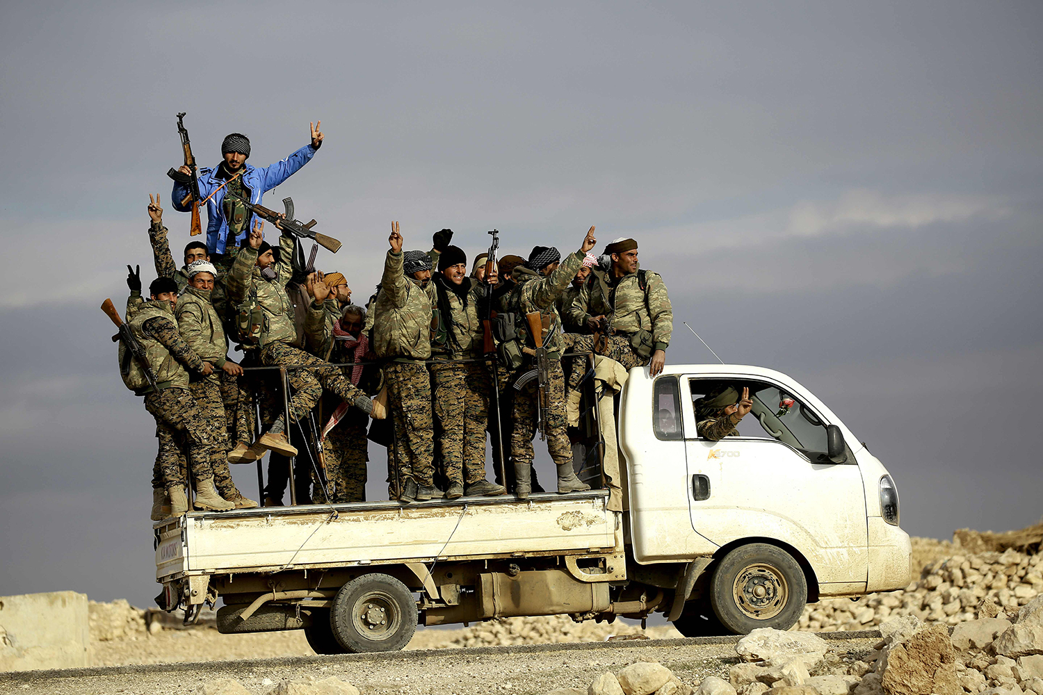 TOPSHOT - Fighters from the Kurdish-Arab alliance, known as the Syrian Democratic Forces, wave from a truck driving through the village of Al-Haymar, located on the western outskirts of the Islamic State (IS) bastion of Raqa, on December 11, 2016. The US-backed alliance announced on December 10 it would launch the second phase of its battle for the IS group's de facto Syrian capital of Raqa. / AFP PHOTO / DELIL SOULEIMAN / TT / kod 444