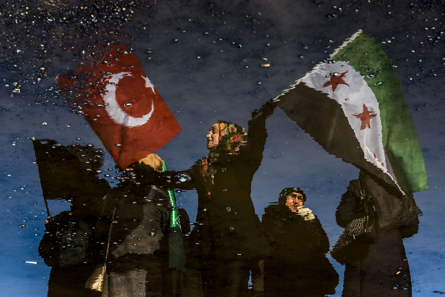A reflection on waste liquid shows a woman wawing Turkish and Free Syrian flags as an aid convoy to Aleppo organized by IHH Humanitarian Relief Foundation is about to leave, on December 14, 2016 in Istanbul. Turkey's aid campaign for the besieged people of Aleppo continued with several nongovernmental organizations sending food, water and clothing. / AFP PHOTO / OZAN KOSE / TT / kod 444