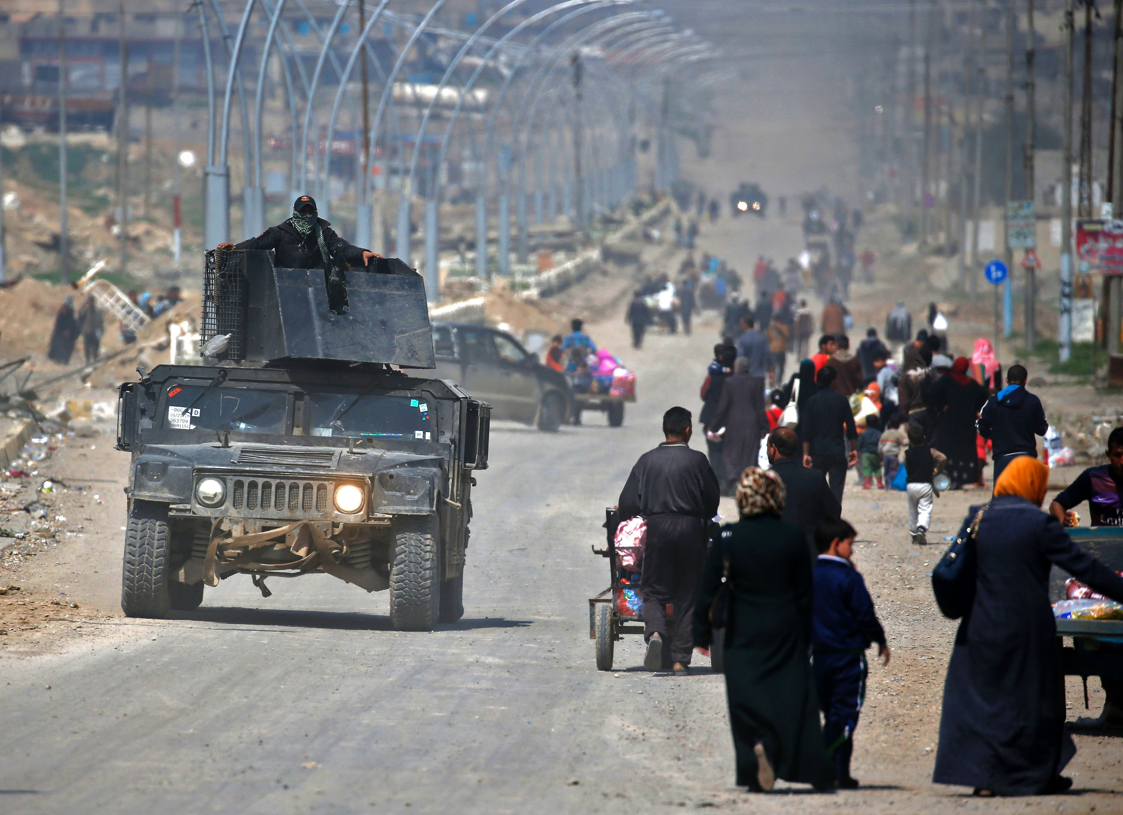 TOPSHOT - Iraqi security forces drive past civilians fleeing their homes in Mosul's old city on March 30, 2017, due to the ongoing battles between government forces and Islamic State (IS) group fighters. / AFP PHOTO / AHMAD GHARABLI / TT / kod 444