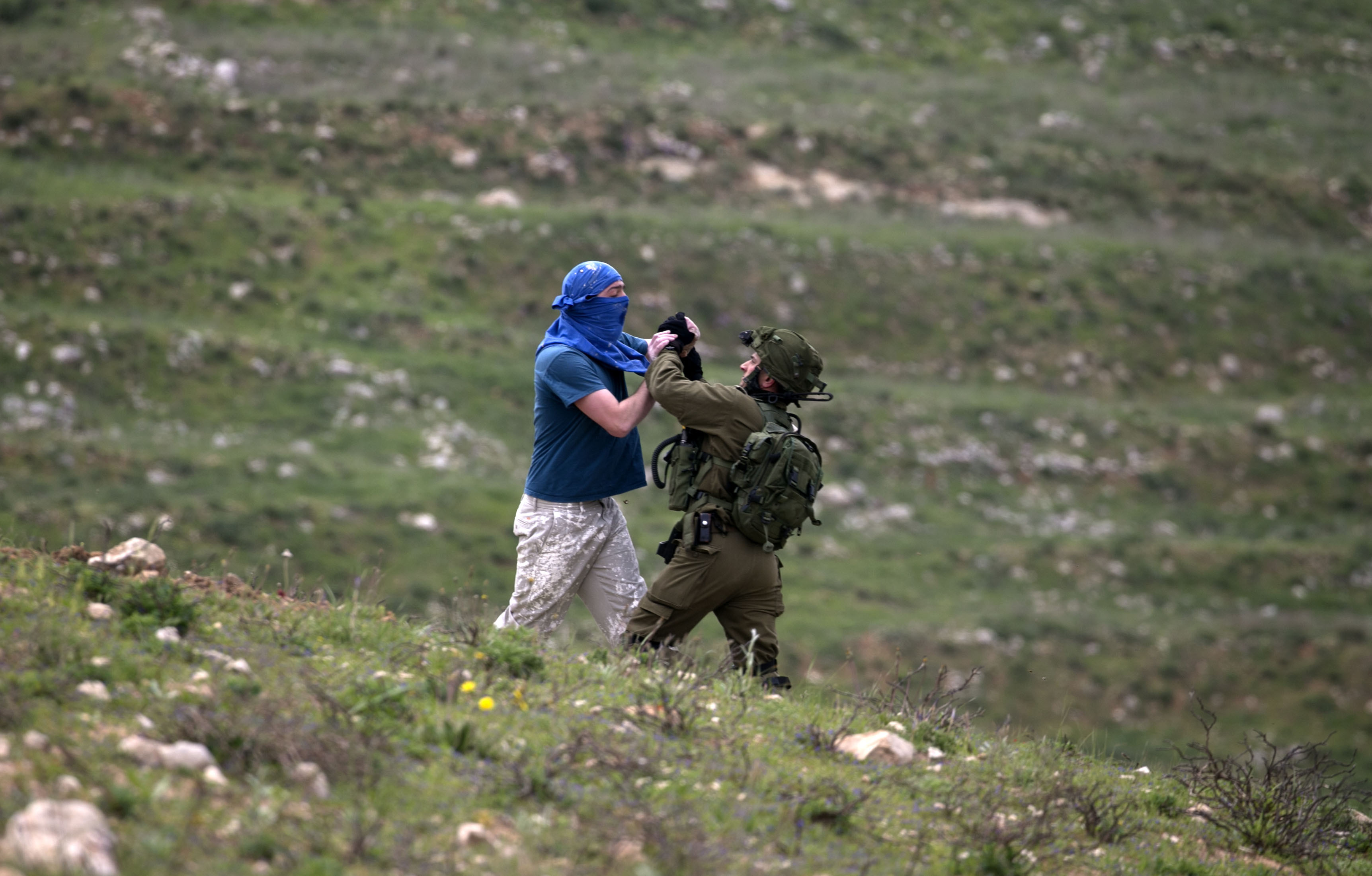 TOPSHOT - An Israeli soldier scuffles with a masked Israeli settler while trying to remove him from the area of a protest by Palestinians on March 30, 2017, to mark land day, in village of Madama south of Nablus in the Israeli occupied West Bank. Land Day marks the killing of six Arab Israelis during 1976 demonstrations against Israeli confiscations of Arab land. / AFP PHOTO / JAAFAR ASHTIYEH / TT / kod 444