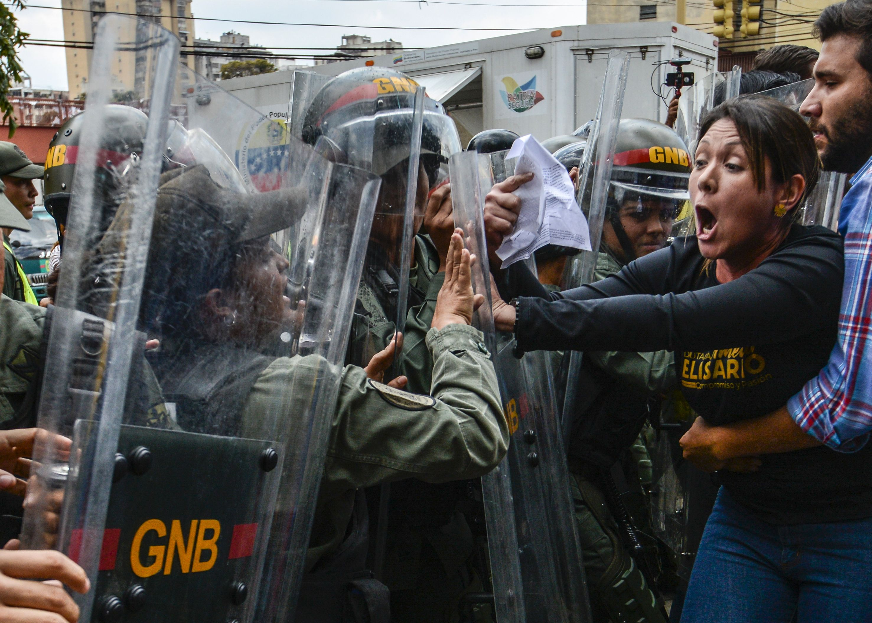 "TOPSHOT - Venezuelan opposition deputy Amelia Belisario (2nd-R) scuffles with National Guard personnel in riot gear during a protest in front of the Supreme Court in Caracas on March 30, 2017. Venezuela's Supreme Court took over legislative powers Thursday from the opposition-majority National Assembly, whose speaker accused leftist President Nicolas Maduro of staging a ""coup."" / AFP PHOTO / JUAN BARRETO / TT / kod 444"
