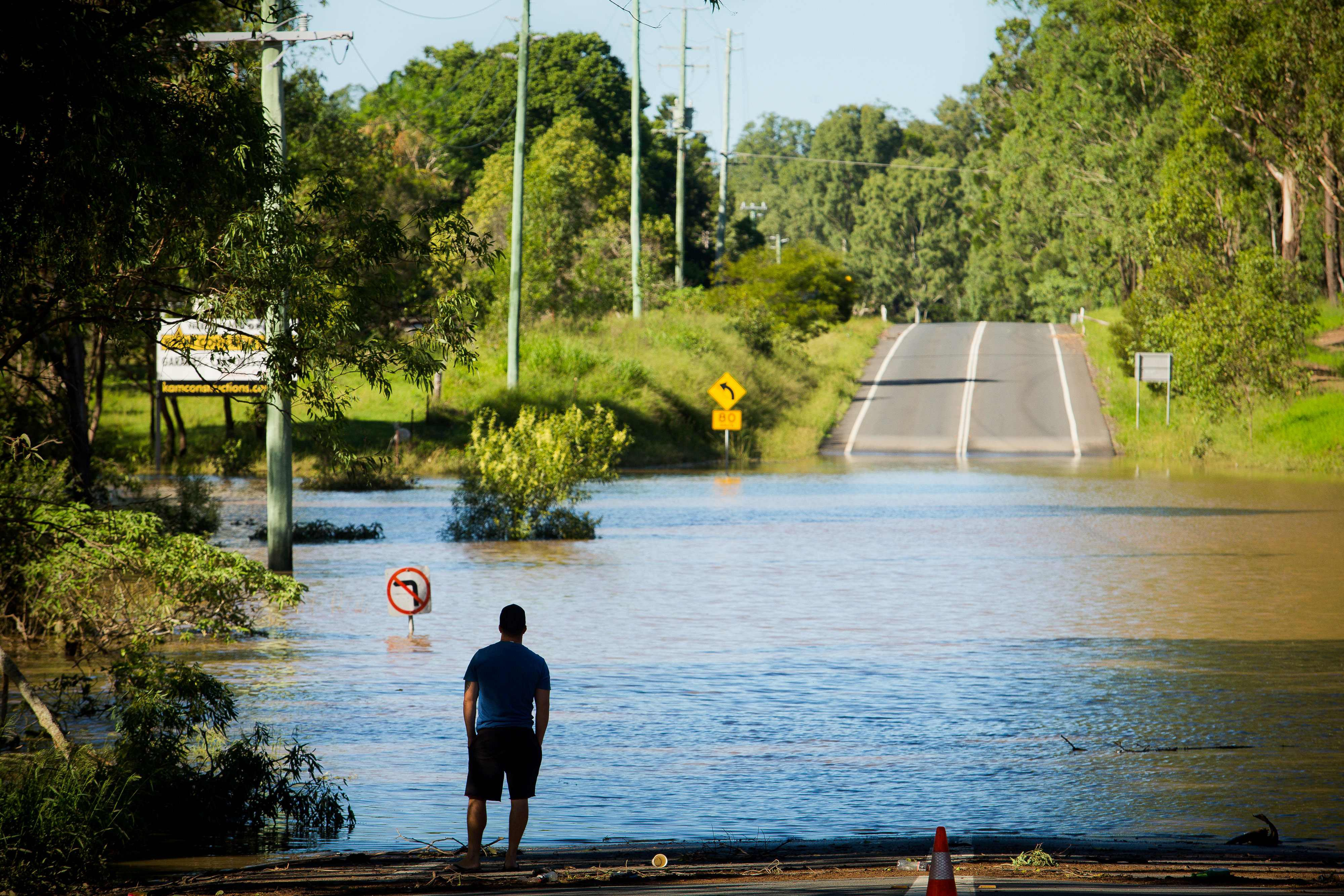 TOPSHOT - A resident looks at a road, submerged under floodwaters caused by Cyclone Debbie, in North MacLean, Brisbane on April 1, 2017. Flooded rivers were still rising on April 1 in two Australian states with two women dead and four people missing after torrential rains in the wake of a powerful tropical cyclone. / AFP PHOTO / Patrick HAMILTON / TT / kod 444