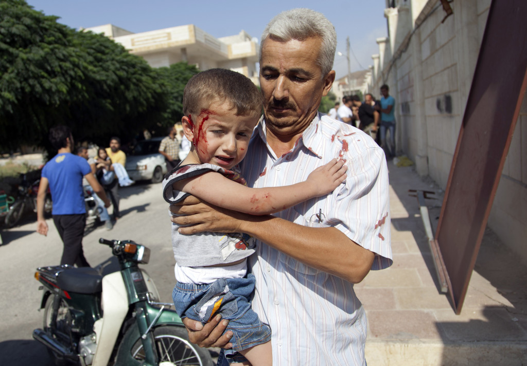 ap foto : khalil hamra : a syrian man carries an injured child to a field hospital after an air strike hit homes in the town of azaz on the outskirts of aleppo, syria, wednesday, aug. 15, 2012. (ap photo/khalil hamra) / scanpix code: 436 mideast syri automatarkiverad