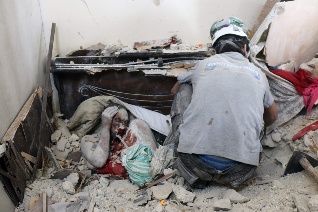 foto : thaer mohammed : topshot - editors note: graphic content / syrian civil defence volunteers, known as the white helmets, retrieve bodies from under the rubble of a building following a reported airstrike on september 23, 2016, on the al-muasalat area in the northern syrian city of aleppo. missiles rained down on rebel-held areas of syria's aleppo, causing widespread destruction that overwhelmed rescue teams, as the army prepared a ground offensive to retake the city. / afp photo / thaer mohammed