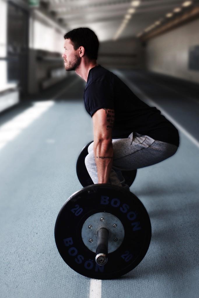 """Behåll bålens anspänning och """"brösta upp"""" kroppens position med stången nära kroppen under övningens startskede."""