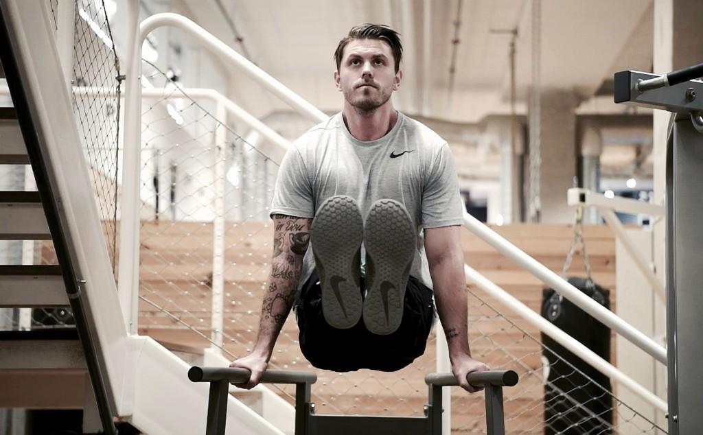 En av de många olika varianterna till övningen. L-Sit utförd i gymmets dipsställning