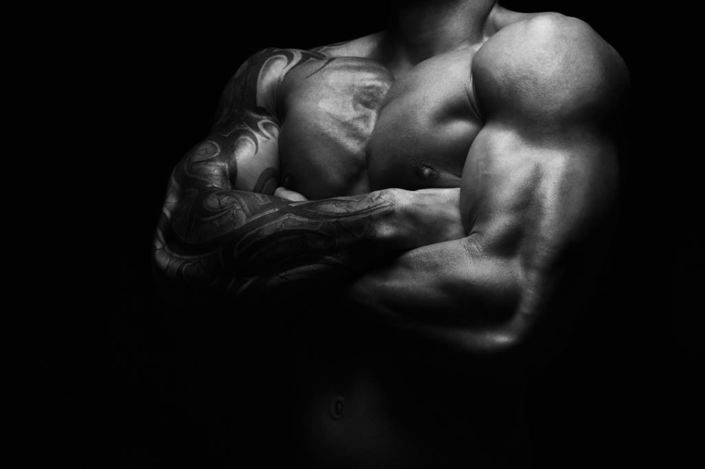 Athletic man's torso. Unrecognizable male fitness model show naked muscular body. Strong muscles and biceps. Studio shot on black background, monochrome, black and white. Bodybuilding concept