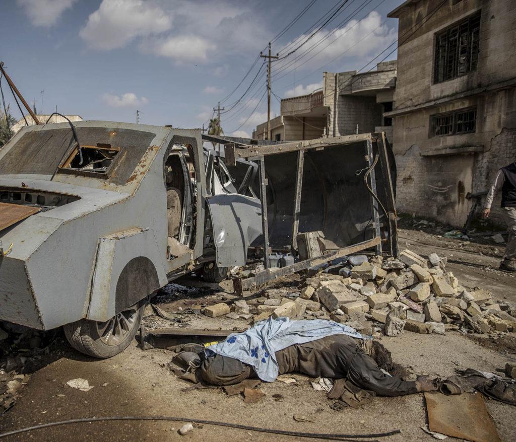 foto : magnus wennman : mosul, irak. en död is krigar ligger intill den bepansrade självmordsbilen som han körde. en stadsdel i västra mosul är totalförstörd efter hårda strider mellan is och irakiska styrkor. flyktingar strömmar ut från stadskärnan i takt med att irakiska armen befriar fler områden.