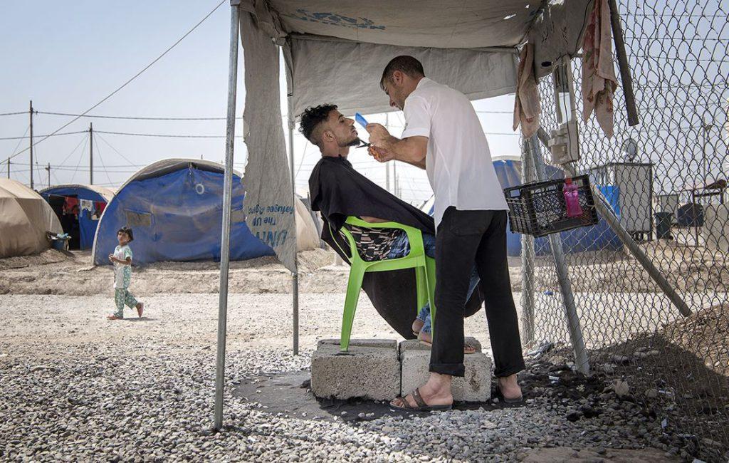 Barberaren Taher Abdelrahim klipper skägget på Haidar Mahmoud i flyktinglägret Khazer under stor koncentration. De båda männen har flytt från Mosul där de tvingades leva under IS våld under flera år. Foto: Jerker Ivarsson