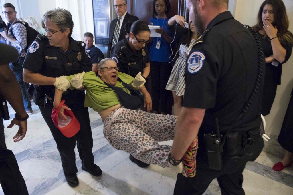 Polisen i Washington arresterar en person som demonstrerar mot ett nytt lagförslag om sjukvårdsförsäkring i USA. AFP PHOTO / SAUL LOEB / TT /