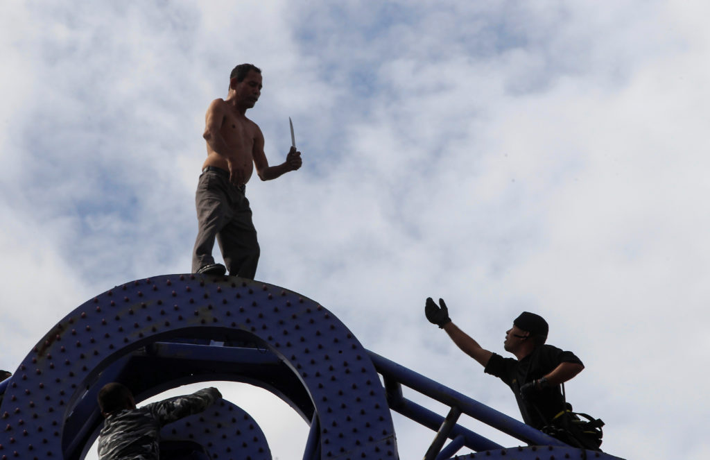 "MANAGUA 2017-07-27 A special forces soldier tries to convince Julio Lopez, carrying a knife in his hand, not to jump off the ""Tree of Life"" metal sculpture to commit suicide, in Managua, Nicaragua July 27, 2017. REUTERS/Oswaldo Rivas      TPX IMAGES OF THE DAY Photo:  / REUTERS / TT / kod 72000"