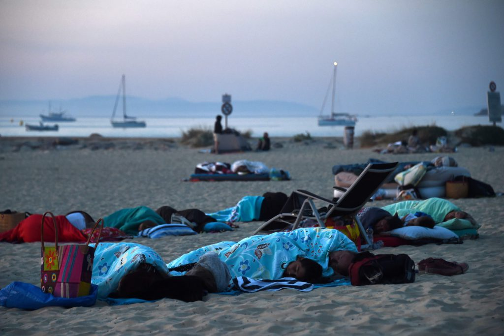 TOPSHOT - People camp and sleep on the beach in Bormes-les-Mimosas, southern France, at sunrise on July 27, 2017 where they took refuge after being evacuated from their campsite due to the fire. Thousands of tourists fled to the safety of public shelters after a fire broke out overnight in the village of Bormes-les-Mimosas, on the Cote d'Azur, and swept towards the area's campsites. Local residents joined firefighters in southern France on July 26, 2017 to battle blazes that have forced over 10,000 people to flee and left chunks of coastal forest a blackened mess. / AFP PHOTO / ANNE-CHRISTINE POUJOULAT / TT / kod 444