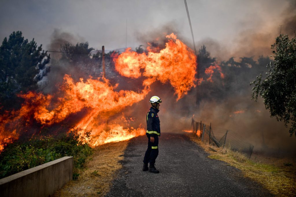 TOPSHOT - A firefighter stands in the middle of a road near flames blazing near the village of Sanguinheira, in Macao, central Portugal, on July 25, 2017.  / AFP PHOTO / PATRICIA DE MELO MOREIRA / TT / kod 444