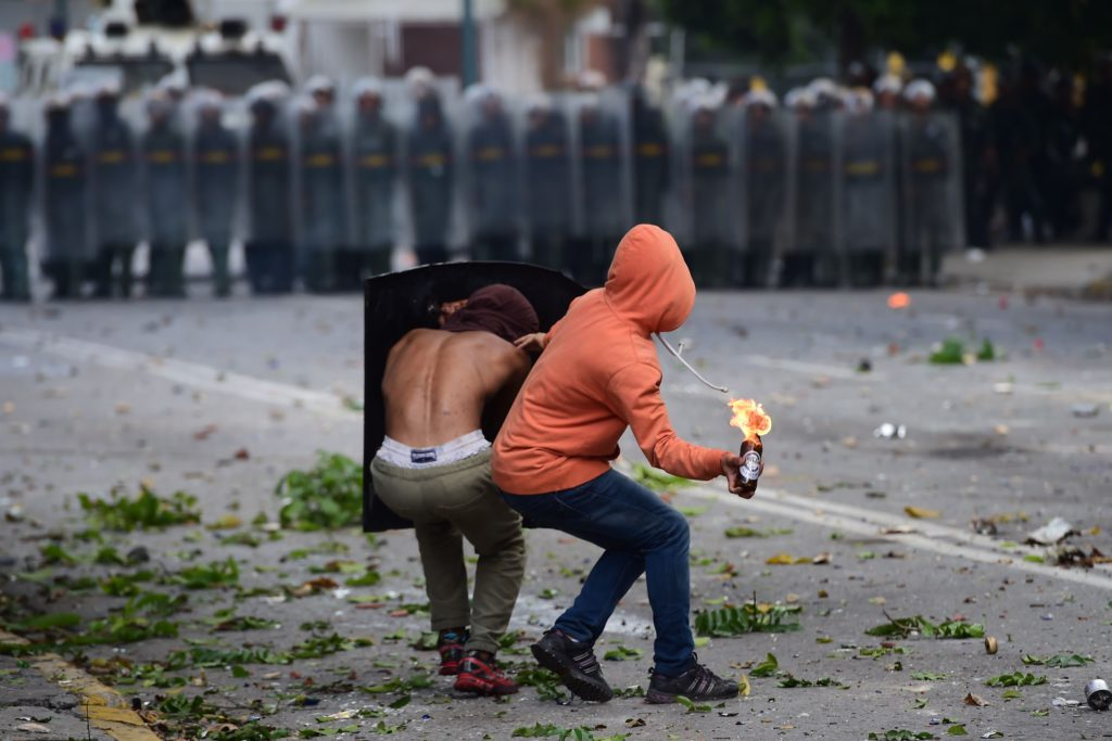 TOPSHOT - An anti-government activist prepares to throw a Molotov cocktail at members of the National Guard during a 48-hour general strike called by the opposition, in Caracas on July 26, 2017. Venezuelans began blocking off deserted streets Wednesday as the opposition launched a 48-hour general strike aimed at thwarting embattled President Nicolas Maduro's controversial plans to rewrite the country's constitution. / AFP PHOTO / Ronaldo SCHEMIDT / TT / kod 444