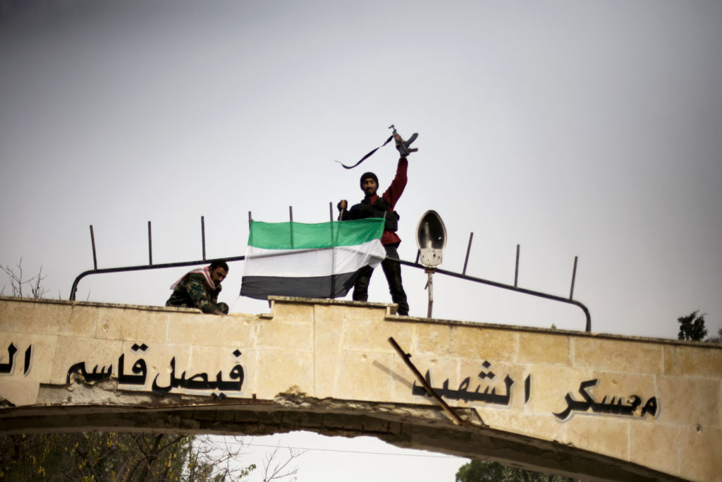 ap foto : manu brabo : free syrian army fighter puts up a fsa flag after heavy clashes with government forces at a military academy besieged by the rebels in tal sheer, syria, sunday, dec 16, 2012 (ap photo / manu brabo)  / scanpix code: 436 mideast syri automatarkiverad