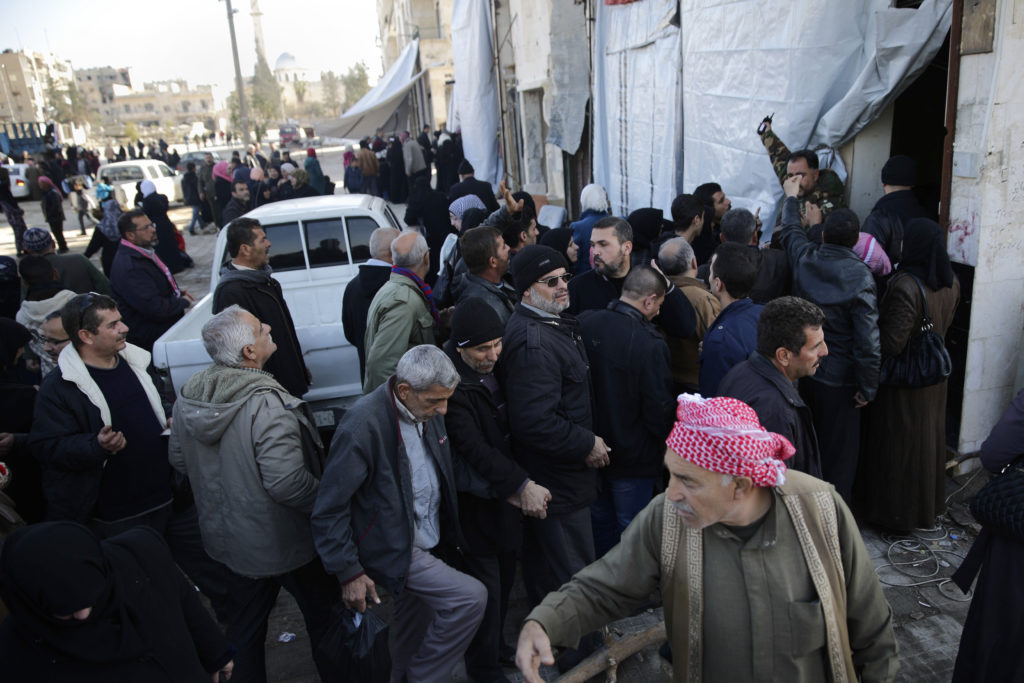 Syrians men displaced from east Aleppo last month wait for a security check to return to their homes in Hanano district in eastern Aleppo, Syria, Sunday, Dec. 4, 2016. On Nov. 26, government forces stormed the Hanano district, their deepest incursion into east Aleppo in more than four years. Abdul-Ghani Kassa, Aleppo's deputy governor, said some 750 families have so far returned the Hanano, a district subjected to wide destruction during government shelling and airstrikes on the area. (AP Photo/Hassan Ammar)