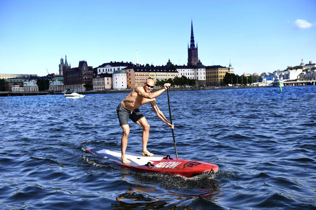 sommar i stockholm. nicklas hultgren pŒ en sup-brŠdan, stand up paddle boarding - stŒpaddling