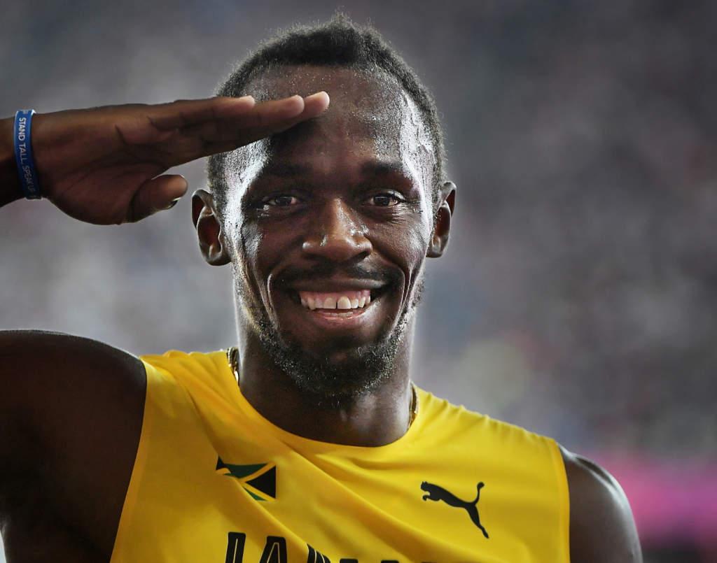 friidrotts-vm 2017 i london. 100 m, herrar, kval. usain bolt, friidrottare jamaica löpare stannar upp i mixade zonen och gör honnör åt sportbladet, tävling action, gestikulerar, glad,